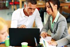 Empresarios que trabajan en el ordenador portátil junto Fotografía de archivo libre de regalías