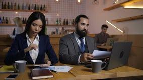 Empresarios que trabajan en los dispositivos digitales en café almacen de video