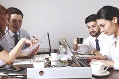 Empresarios que trabajan junto en oficina fotos de archivo
