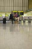 Empresarios que usan el ordenador portátil en aeropuerto foto de archivo