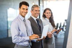 Empresarios que usan el teléfono móvil, el top del revestimiento y la tableta digital Imágenes de archivo libres de regalías