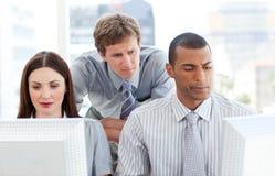 Empresarios serios que trabajan en los ordenadores imagen de archivo