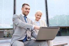 Empresarios sonrientes con el ordenador portátil al aire libre Imagen de archivo libre de regalías