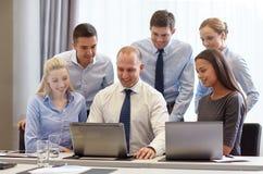 Empresarios sonrientes con los ordenadores portátiles en oficina fotos de archivo libres de regalías