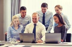 Empresarios sonrientes con los ordenadores portátiles en oficina foto de archivo libre de regalías