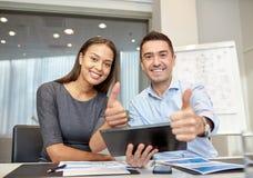 Empresarios sonrientes con PC de la tableta en oficina Foto de archivo