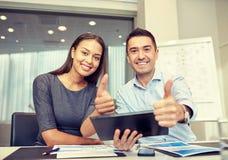 Empresarios sonrientes con PC de la tableta en oficina Imagen de archivo