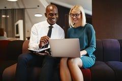 Empresarios sonrientes que se sientan en una oficina que trabaja en un ordenador portátil fotografía de archivo