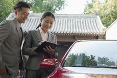 Empresarios sonrientes que trabajan al aire libre en coche rojo Fotografía de archivo