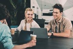 empresarios sonrientes que trabajan en la tabla con los ordenadores portátiles y las tazas de café en moderno imagen de archivo libre de regalías