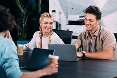 empresarios sonrientes que trabajan en la tabla con los ordenadores portátiles y las tazas de café en moderno fotografía de archivo libre de regalías