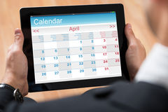 Empresário Looking At Calendar na tabuleta de Digitas Fotos de Stock