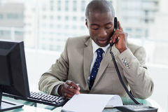 Empresário que faz um telefonema ao ler um original Imagens de Stock