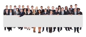Empresários multi-étnicos que guardam o quadro de avisos vazio Fotografia de Stock Royalty Free