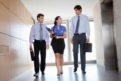 Empresários que andam no corredor do escritório Fotos de Stock