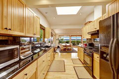 Empressive kitchen interior with shiny black granite tops. Empressive kitchen room with black shiny couter tops and skylight. View of dining area with exit to Stock Photos