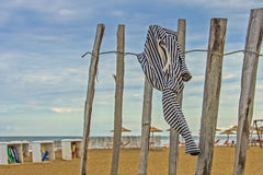 Empry beach with marine striped shirt hanging on the fence. Stock Photos