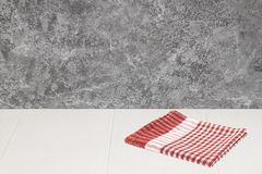 Empte wooden desk table over grey grunge wall and red napkin