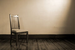 Emptiness. An old chair sits in an empty room Stock Photos