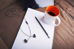 Emptiness and no inspiration for graphic designer. Empty notepad as a symbol of hard work of creation and headphones for music. Royalty Free Stock Image