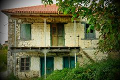 Empty and Abandoned Greek Mountain Village House. An empty and abandoned two level Greek mountain village stone house with green wooden window shutters and doors stock photo