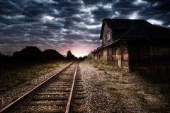 Empty and abandoned train station at night. Sunset in background Royalty Free Stock Image