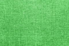 Burlap background colored in green and white blend royalty free stock image