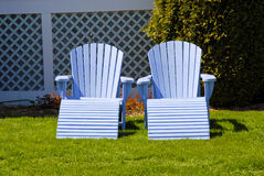 Empty Adirondacks. Front view of two light blue adirondack chairs, empty on green grass Royalty Free Stock Photo