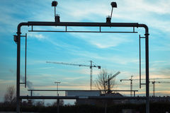 Empty advertisement structure with cranes against blue sky Royalty Free Stock Photography
