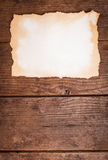 Aged paper on wood. Empty aged paper on the wooden background royalty free stock photo