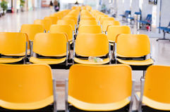 Empty airport chairs. Empty yellow chairs in the airport Stock Photo