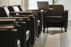 Empty Airport Seating and Laptop. A row of empty seats in an airport with a laptop on a table Royalty Free Stock Image