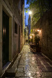 Empty alley at Split's old town at dark. Narrow and empty alley with few cafe tables at the old town in Split, Croatia, at dark after rain Royalty Free Stock Photos