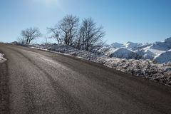Empty alpine mountain road in winter, blue sky Stock Images