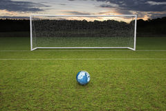 Empty amateur football goal blue leather football. Empty amateur football goal posts,nets and a blue leather football with a map of the globe on the ball royalty free stock photography
