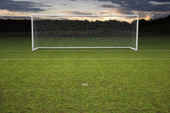 Empty amateur football goal posts. And nets shot at sunset royalty free stock photo