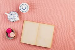 Empty ancient small book open with pink french macaroons and chinaware teapot on a pink tablecloth. Empty ancient small book open, Pink french macarons or royalty free stock photos