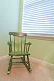 Empty Antique Child's Rocking Chair. Empty, green, antique rocking chair of a child in the corner of a bedroom. Vertical. Copy space Royalty Free Stock Images