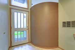Empty apartment interior features entrance foyer with tan wall. Royalty Free Stock Photo