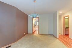 Empty apartment interior features white walls and beige carpet floor.  Stock Photo
