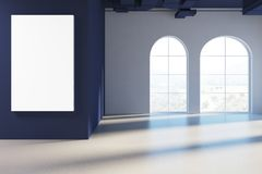 Empty arch windows room, blue ceiling, poster. Empty room with white and dark blue walls, arch like windows and a concrete floor. There is a large vertical Stock Photo