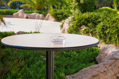 Empty ashtray on one legged, round table in the garden.  Royalty Free Stock Images