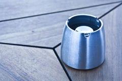 Empty ashtray on the table. Iron ashtray on wooden table Stock Photos