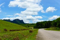 empty asphalt country road along the wall of dam with green grass and blue sky with clouds and mountain background in countryside. Stock Image