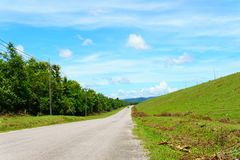 empty asphalt country road along the wall of dam with green grass and blue sky with clouds and mountain background in countryside. Stock Photo