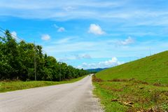 empty asphalt country road along the wall of dam with green grass and blue sky with clouds and mountain background in countryside Stock Images