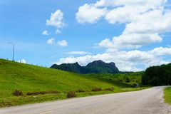 empty asphalt country road along the wall of dam with green grass and blue sky with clouds and mountain background in countryside Royalty Free Stock Image