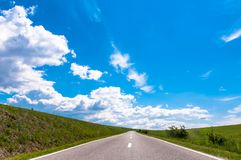 Empty asphalt country road blue sky. Empty asphalt country road, wild rose bush on roadside, blue sky, gathering storm clouds Royalty Free Stock Images
