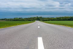 Empty asphalt country road with green grass fields under stormy clouds in the summer Stock Photos