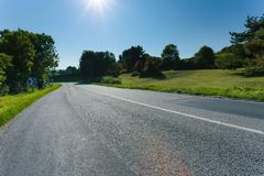 Empty asphalt country road passing through green fields and forest. Countryside landscape on sunny day with sunbeams in Royalty Free Stock Photos